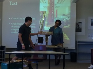 Students defend their chair design to the class
